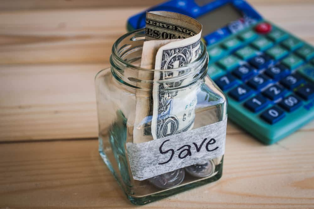 a jar with money with the word Save on the front and a calculator in the background
