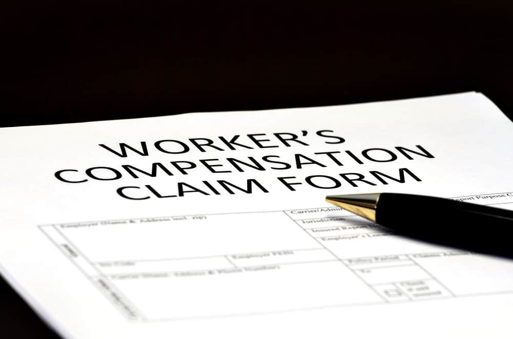pen sits on a Worker's Compensation Claim Form