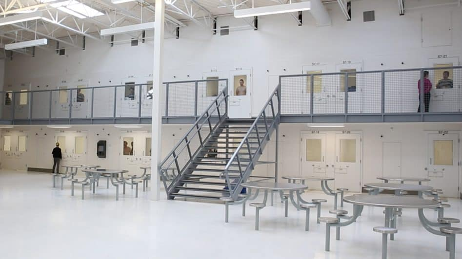 white interior of jail common area with metal stools, tables and staircase