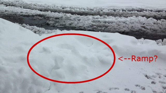 snow covered curb with a red circle and text pointing to an area where there may be a ramp but it is impossible to tell because of the snow