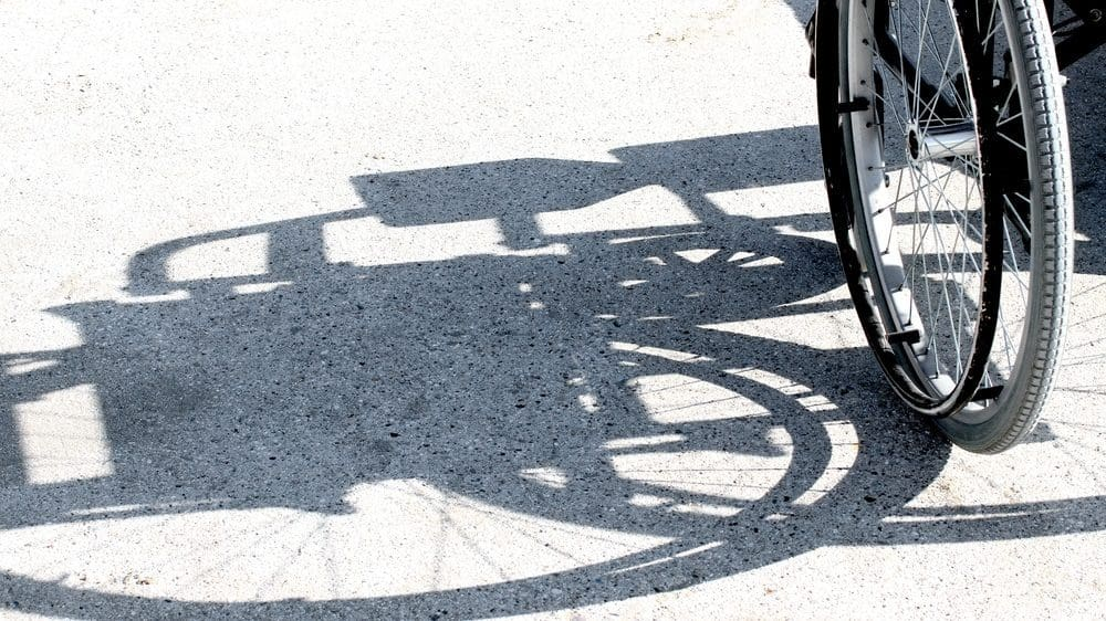 Side of a wheelchair, mainly the wheel, giving off a shadow of the wheelchair on the ground.