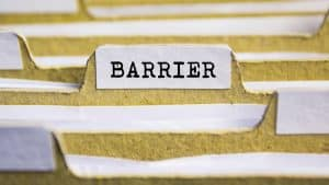 """Yellow file folders filled with papers. One folder is labeled """"barrier."""""""