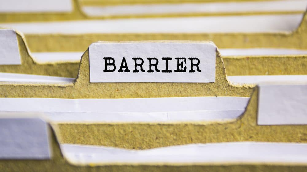 "Yellow file folders filled with papers. One folder is labeled ""barrier."""