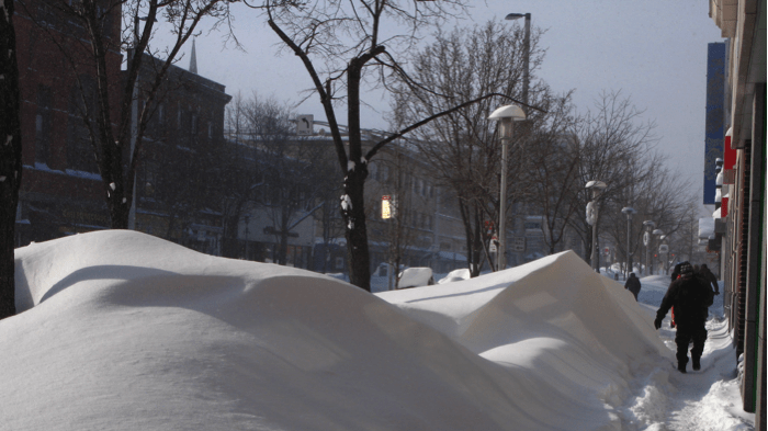 A large snow drift covering a sidewalk, making it impassable.