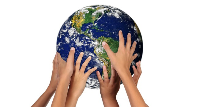 Hands of many different skin tones holding up the world.