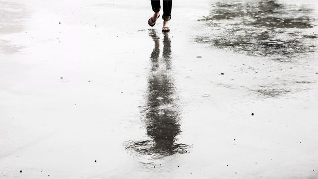Person looking at their reflection on pavement that is wet. You can only see the actual person's feet. They are wearing flip-flops.