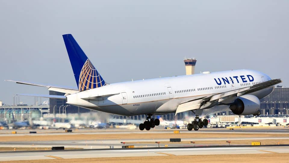 A United airplane hovering over a runway during the daytime.