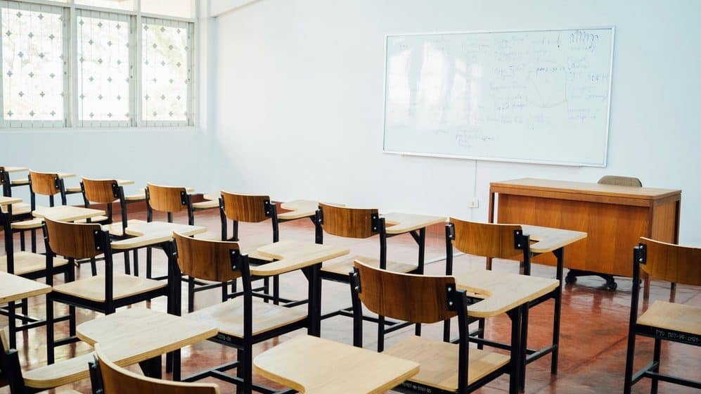 Empty School classroom with wooden desks, chairs, and whiteboard