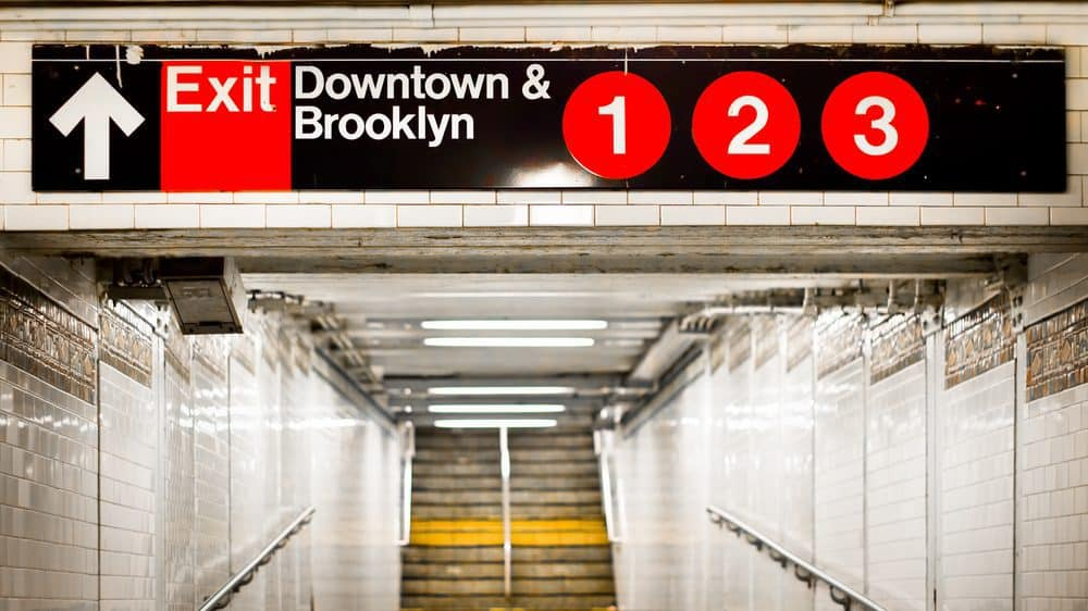 "Photo of hallway leading to steep stairs. Above is a sign that says ""Exit, Downtown & Brooklyn - 1, 2, 3."""