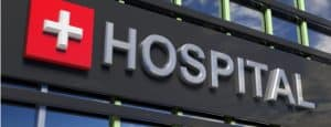 """A close-up of a black sign on a building that says """"Hospital"""" in gray letters. Next to the text is a red square with a gray cross symbol on it."""