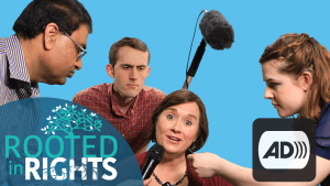Screenshot of a scene from the Like the Mic video that features 3 individuals holding different types of microphones in front of a woman's face