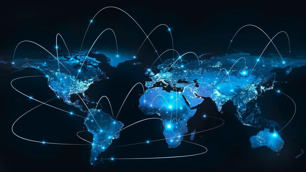 A glowing blue flat map of the world against a black background. There are several points of light, all connected by curved lines to indicate technological connections across the map.