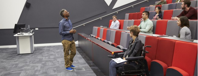 A group of students in a lecture hall, sitting with several open seats in between each student. A student in a power chair sits at the bottom of the stadium-style lecture hall seating, separate from peers.