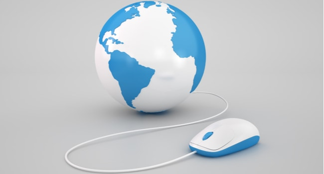 A computer mouse connected by a wire to a globe depicting some of the earth.