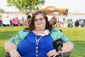 Photo of Carrie Ann Lucas Carrie wearing blue and teal cat eye glasses, curly hair, a blue dress, long necklace, and a multicolored blue and teal jacket. Carrie's trach and ventilator tubing is pictured, along with portions of her wheelchair controller.