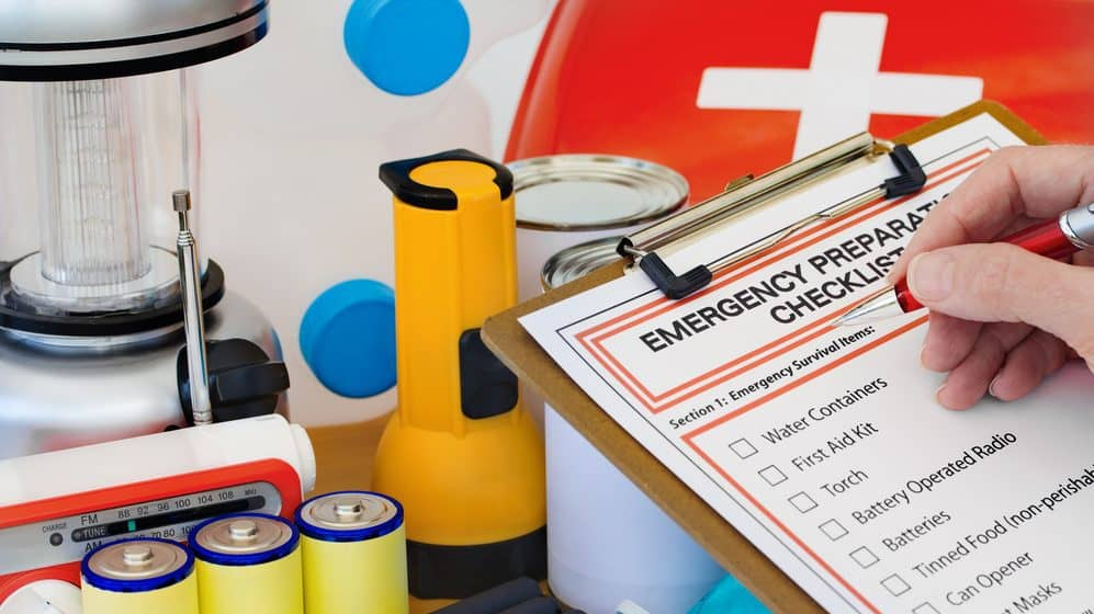 Emergency supplies including flashlight, radio, and waterbottle. A person is writing on an emergency preparedness checklist attached to a clipboard