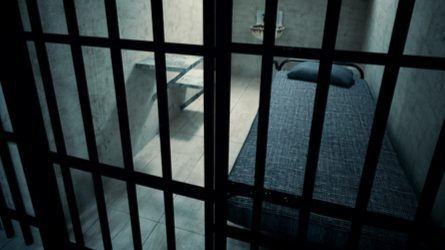 A view of a single-occupancy prison cell through the metal bars. Inside is a bed, toilet, and sink.