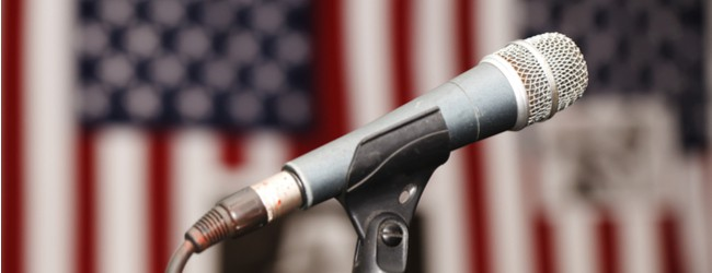 A photo of a microphone on a stand in front of blurred American flags in the background.