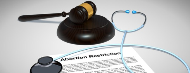 "A paper that is titled ""abortion restriction rests on a table, with a stethoscope draped across it and a gavel next to it."