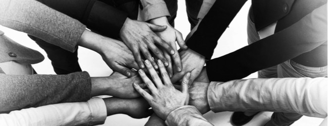 A black and white photo of hands of different skin tones piled together in a circle showing solidarity.