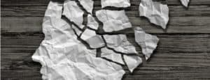 Crumpled paper in the shape of a head rests on a wood surface. The paper making up the brain is fragmented.