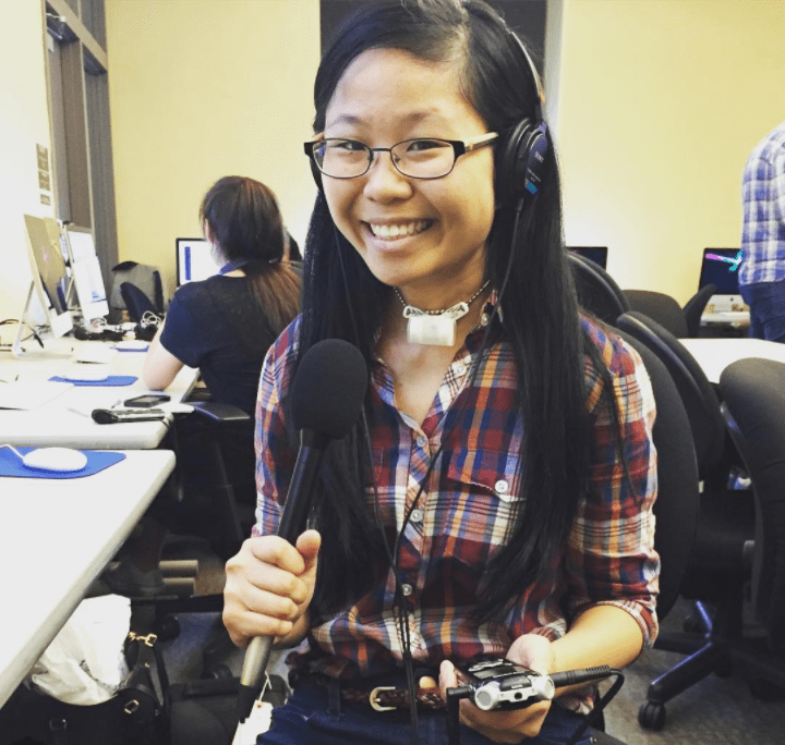 A Chinese American woman with glasses and a tracheostomy tube smiles at the camera, wearing a red and blue plaid shirt and blue jeans with a thin belt. She is wearing a black audio headset and holding up a padded microphone in her right hand and a black recorder in her left hand. She's sitting in a classroom with Mac computers and students sitting or bustling in the background.
