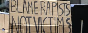 "A cardboard sign being held up. The sign says ""blame rapists, not victims."""