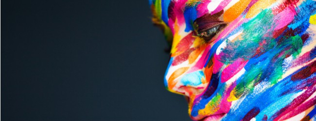 A photo of a person whose face is painted with lines in a rainbow of colors