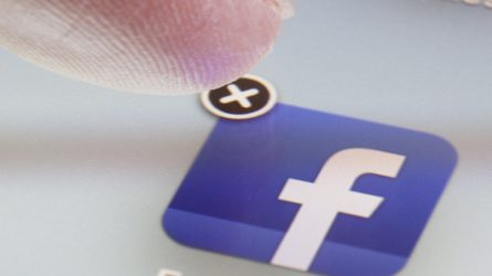"""A finger hovers over the Facebook app icon, poised to press the """"x"""" to delete the app."""