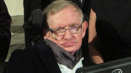 Photo of Stephen Hawking looking directly at camera. He is in a jacket and scarf and his assistive communication device is in front of him.
