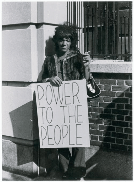 "Marsha P. Johnson, a Black trans woman, stands with a sign reading ""POWER TO THE PEOPLE."" She is wearing a fur coat and holding a cigarette."