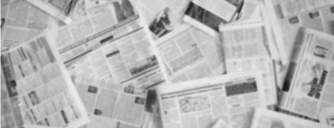 A pile of newspapers spread out over one another. The text is blurred and unreadable.