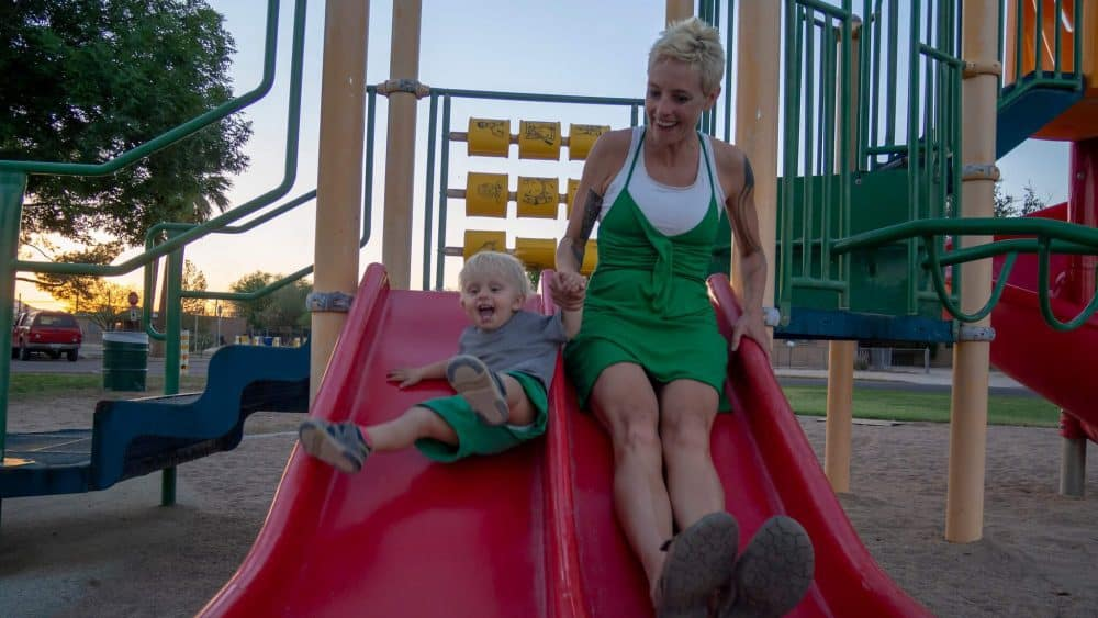 A photo of Anna and her toddler son going down a big red slide together.