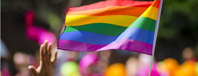 A supporting hand waves in front of a rainbow flag flying on the sidelines of a summer gay pride parade