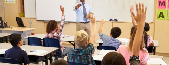 A teacher at the front of the class pointing who a student whose hand is raised. There is a group of students sitting in front of the teacher at their desks.