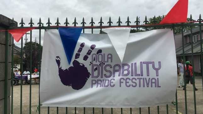 "Sign with a handprint that reads ""NOLA Disability Pride Festival"" hanging on a wrought iron gate."