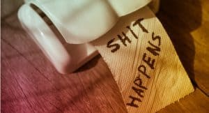 "A photo of a toilet paper dispenser with toilet paper coming out of it. On the toilet paper it says ""shit happens."""