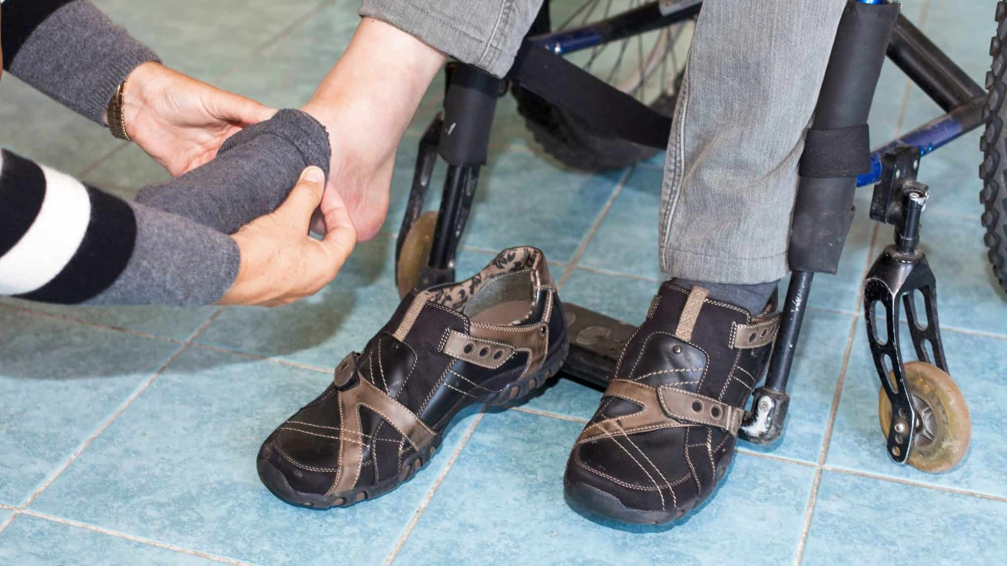 Photo showing a person kneeling down, assisting a person sitting in a wheelchair with putting on a sock.