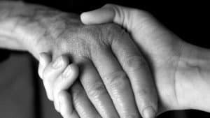 Black and white photo of two people holding hands, one is an older person and one a younger person. The photo is focused just on the hands.