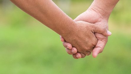 two hands holding together on blurred green background