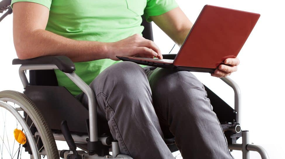 A person in a manual wheelchair holds a red laptop in their lap.