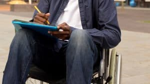 A person in a wheelchair holding folders and a pen