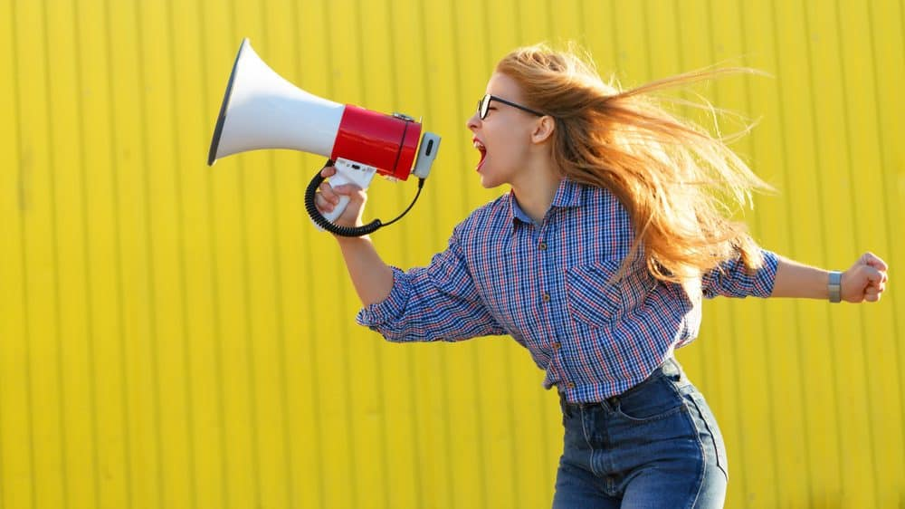 A woman is yelling into a megaphone, in an empowered pose.