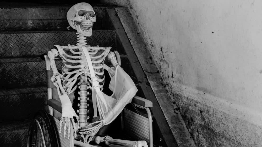 Black and white photo of skeleton sitting in a hospital-style wheelchair in front of stairs.