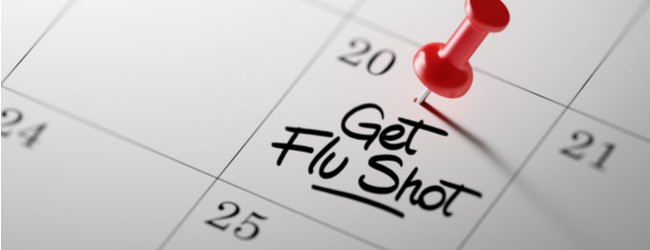 "Image of a calendar with the words ""get flu shot"" written down in the box for the 20th. There is a red push pin on top of it."