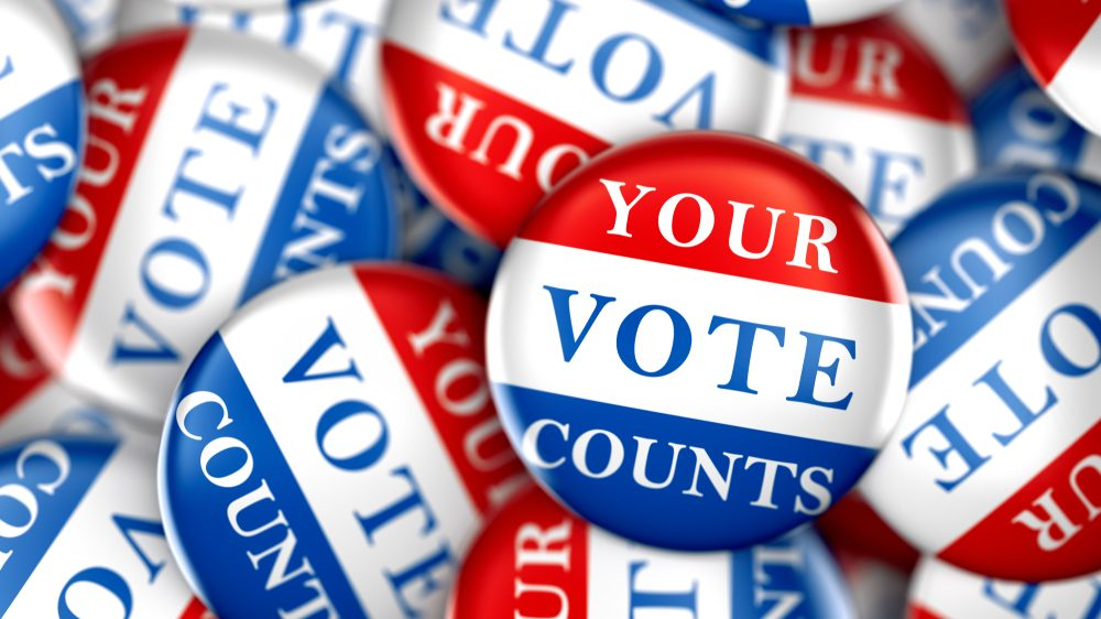A pile of red, white, and blue buttons that say 'Your vote counts.""