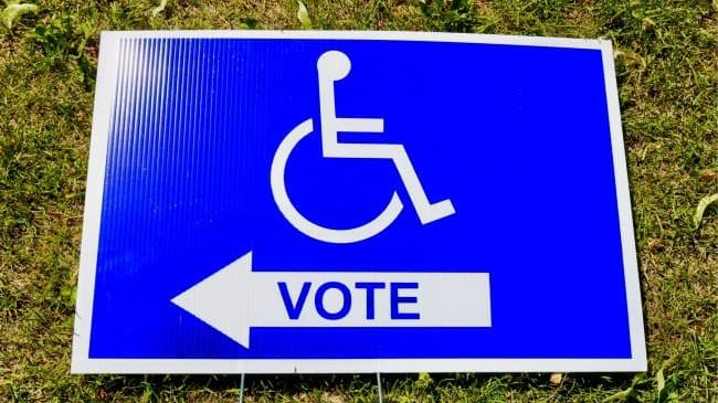 A bright blue sign mounted in grass that has an accessible icon and an arrow that says vote on it.