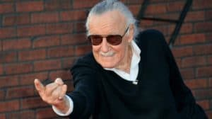 Photo of Stan Lee in a black suit and sunglasses, pointing his finger forward.