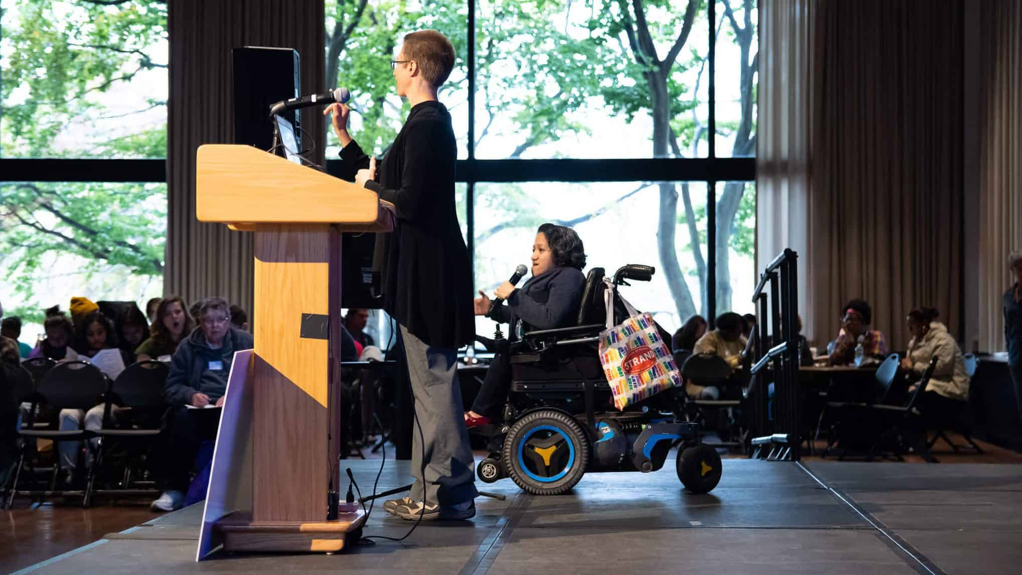 Laura Kiesel sits in her power chair and speaks into a microphone, next to another speaker on a stage in front of an audience.