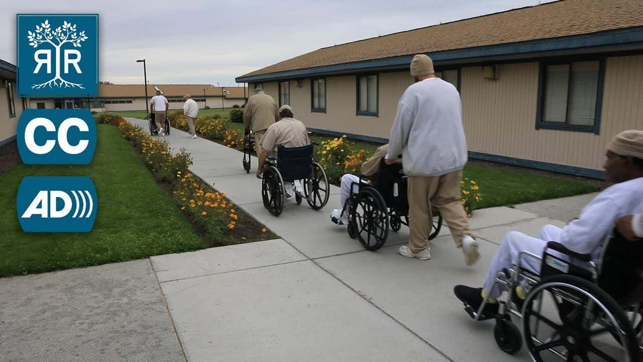 A row of inmates move down a walkway. Several are in wheelchairs. Another uses a walker.